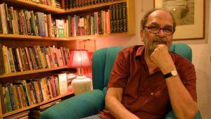 Mies nojaa käteensä tuolissa kirjahyllyn edessä