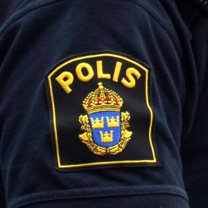 Två svenska poliser står bredvid varandra. Men ser deras emblem.