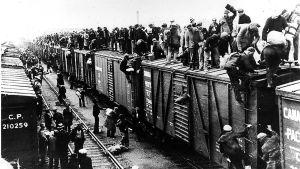Ihmisiä seisoo ja istuu täyden junan katolla ratapihalla.