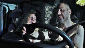 Nainen ja mies istuvat asuntoauton ohjaamossa alasti. Kuvassa ovat näyttelijät Niina Hosiasluoma ja Miko Kivinen.