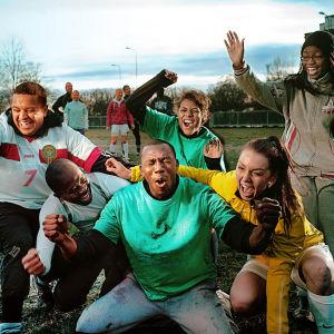Unga människor med olika etniskt ursprung som tillsammans hurrar på en gräsplan.