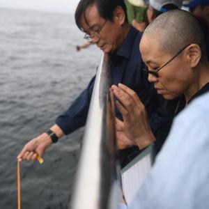 Liu Xiaobos änka Liu Xia (till höger) tillsammans med Liu Xiaobos yngre bror sprider den avlidne fredspristagarens aska i havet.