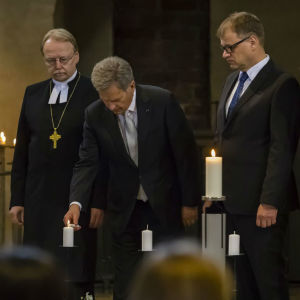 President Saulli Niinistö tänder ett ljus under minnesstund för offren i inbördeskriget. Statsminister Juha Sipilä, ärkebiskop Kari Mäkinen och Vänsterförbundets riksdagsledamot Li Andersson står intill.