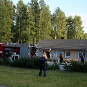 Brandbil och polis utanför radhuslägenhet.