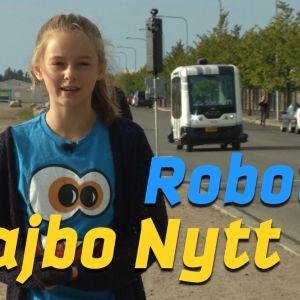 Maddie står vid vägkanten med en robotbuss i bakgrunden
