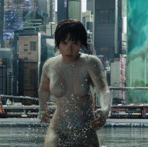 Major (Scarlett Johansson) springer i vatten, i bakgrunden skyskrapor.