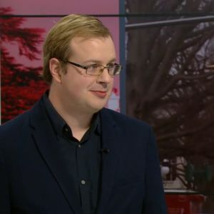 Oscar Winberg i tv-nytts studio. Winberg är doktorand i allmän historia vid Åbo Akademi, med specialintresse för USA.