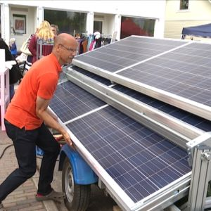 André Lindholm öppnar solpanelerna på Pargas mobila solvagn.