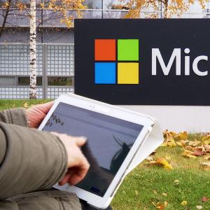 Microsoftin logo, jonka edessä tablettia pitelevä käsi.