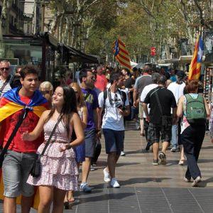 Jalankulkijoita ja lippuja Barcelonan Ramblalla.