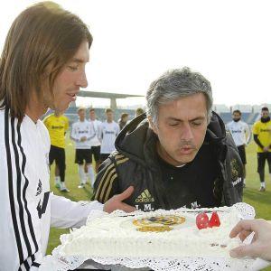 José Mourinho puhaltaa kynttilöitä syntymäpäiväkakusta, jota pelaajat kannattelevat.