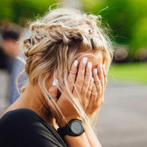 Nainen istuu puistonpenkillä ja pitää kämmeniä kasvojensa edessä.