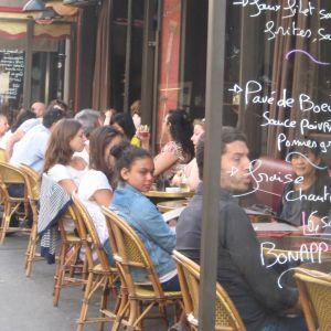 Pariisilaisen kahvilan ulkoterassi, ikkunassa käsinkirjoitettu lounaslista.