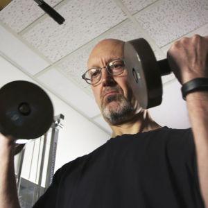 Person lyfter tyngder med ett aktivitetsarmband.