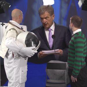 Presidentti Niinistö katsoo astronauttipukuista miestä.