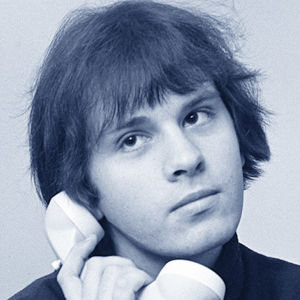 Toimittaja Jorma Elovaara puhelimen kuuloke poskellaan, upotuksena mainos Vesimiehen aika -kaseteista (kollaasi).