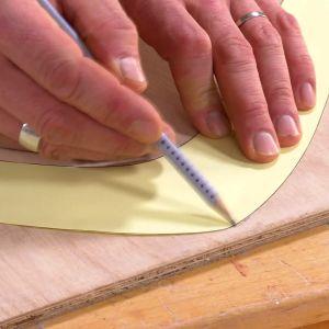 Jim ritar upp bumerangmodellen på fanérskivan