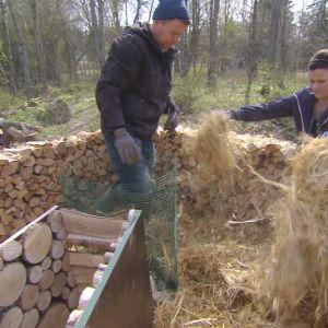 Owe Salmela och Camilla Forsén-Ström lägger halm i nyckelhålsträdgården
