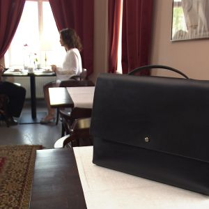 En svart läderportföj i förgrunden på ett bord.
