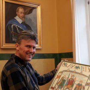 Historielektor Karl-David Långbacka och en kopia av Bayeuxtapeten