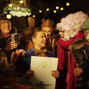 Gänget i småfolksbyn har samlats runt lillspiken som håller i en teckning med ett ljus
