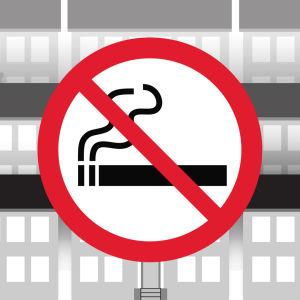 Grafiikka: tupakointi kielletty -merkki, taustalla kerrostaloja.