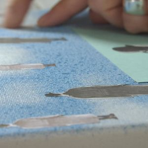 Camilla limmar fast profiler av en man i olika storlekar på den grundmålade målarduken.