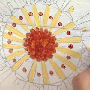 Målar med acrylfärg en mandala på en dörr