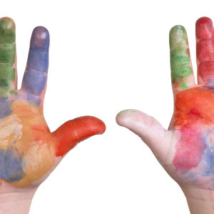 ett dagisbarns händer uppe i luften, täckta av olika färger