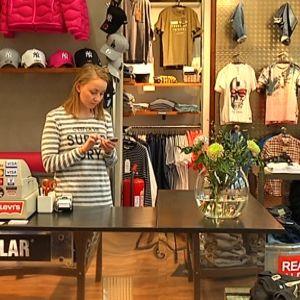 En kvinna tittar på sin telefon i en klädbutik.