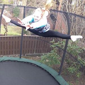 Flicka studsar högt i luften på trampolin