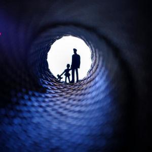 en animerad bild med ett barn och en man i ändan av en mörk tunnel