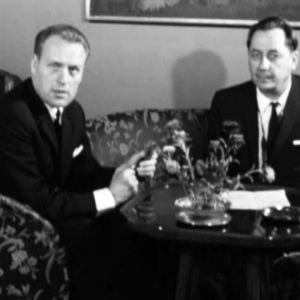 Majuri Wayne Aho (oikealla) ja tv-toimittaja istuvat sohvaryhmässä kukilla koristetun pienen pöydän ääressä ja katsovat kameraan.