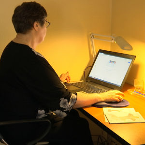 Ingrid Hollmérus-Nilsson sitter framför en dator.