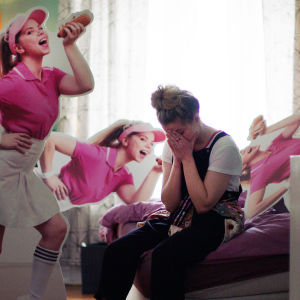 Nuoret ja lupaavat -sarjan Alex (Alexandra Gjerpen) istuu sängyllä ja peittää kasvonsa käsiinsä. Vierellään pahvimainoksia, joissa hän poseeraa hot dogin kanssa.