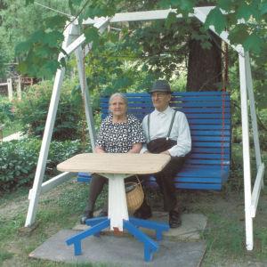 Vanha pariskunta istuu pihakeinussa.