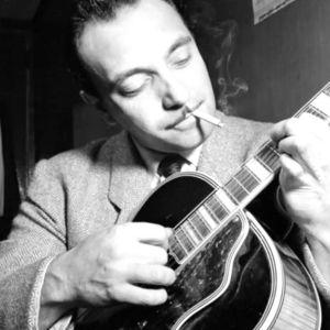 Django Reinhardt spelar gitarr medan han röker en cigarrett.
