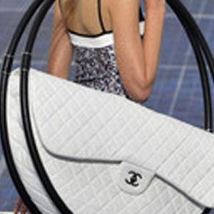 Valtava Chanelin valkoinen käsilaukku mallin olkapäällä.