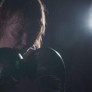 Tuhkimotarinoiden Eijasta tummasävyinen kuva nyrkkeilemässä.
