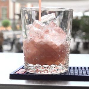 En alkoholfri, rosa drink hälls i ett glas.
