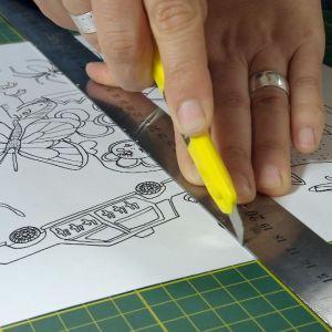 Teckning skärs mitt itu med skärkniv och linjal.