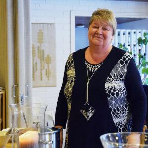 En bild på en kvinna i en sal, framför henne står mat på ett bord. I hörnet av bilden finns en stämpel där det står vardagshjältar. Kvinnan heter Mona Andersson.