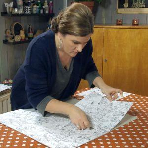 Camilla Forsén-Ström limmar fast tecknade mönsterdelar på kartong.