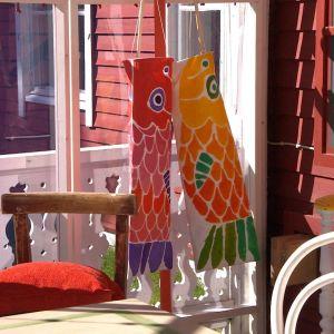 Vindsockor med karpfisk motiv hänger på en veranda.