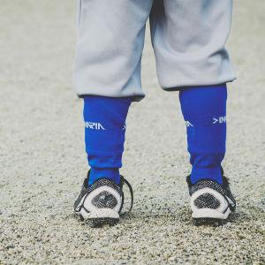 Lapsi seisoo hiekkakentällä jalkapallokengät jalassa.