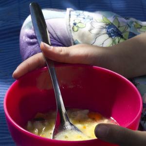 En skål med fisksoppa i ett barns händer. Barnet verkar sitta på en blå filt.