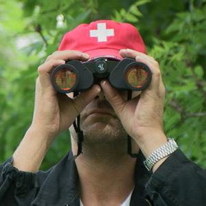 Roman Schatz katsoo kiikareilla kameraan päin