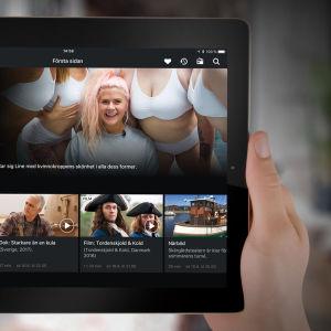 Användare håller i en pekplatta med Yle Arenan-appens förstasidesvy öppen.