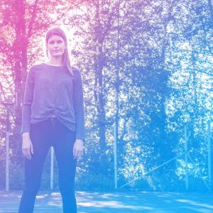 Sara Jakobsén står på en korgbollsplan. I bakgrunden syns solstrålar och en stängsel av metall.