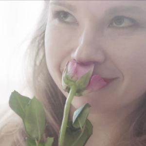 Anna-Riikka Rajanen roolihahmossaan haistelee vaaleanpunaista ruusua vaaleassa kuvassa.